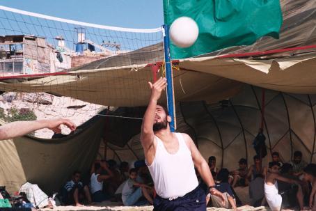 Mies lyö lentopalloa verkon yli. Hänen takanaan teltassa istuu useita ihmisiä.