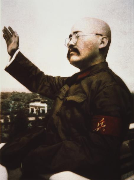 Kaljupäinen mies, jolla on viikset ja pyöreät silmälasit, on kohottanut oikean kätensä ylös. Hän katsoo poispäin kamerasta.
