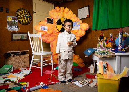Pieni poika valkoisissa vaatteissa seisoo huoneessa sakset kädessään. Hänen takanaan on oranssi sienipilveä muistuttava pahvinen rakennelma. Siinä on ydinjätteestä varoittava kelta-musta merkki.