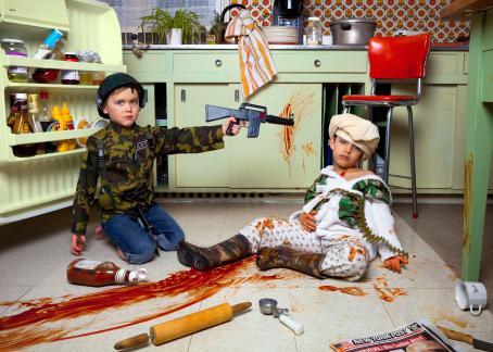 """Keittiön lattialla on kaksi lasta. Toisella on päällään armeijan vaatteet, ja hän osoittaa leikkiaseella toista lasta, joka on pukeutunut maastokuvioiseen kylpytakkiin ja saappaisiin. Hänestä lähtee punainen vana lattiaa pitkin, minkä vieressä on ketsuppipullo. Kuvan alareunassa näkyy New York Post, missä on otsikko """"Bin Laden dead""""."""