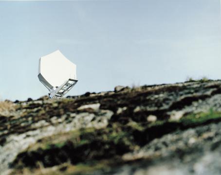 Etualalla epätarkkaa kivikkoista maisemaa, taaempana valkoinen lautasantenni sinistä taivasta vasten.