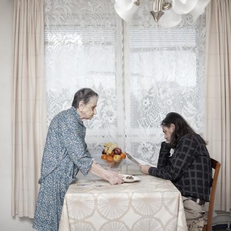 Keittiönpöydän ääressä istuu pitkähiuksinen mies lukemassa lehteä. Toisella puolella pöytää seisoo vanha nainen, joka on laittamassa pöydälle ruokalautasta.