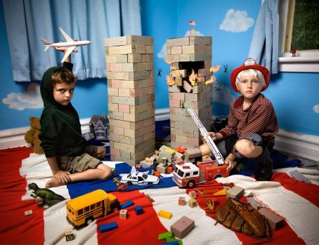 Lastenhuoneen lattialla istuu kaksi lasta. Heidän välissään on rakennuspalikoista rakennettu kaksi tornia, joista toisessa on aukko, josta tulee tulenlieskoja ja tippuu ihmisiä. Toisella lapsista on musta huppari ja hän pitää kädessään ylhäällä lentokonetta, toisella lapsista on palomiehen kypärä päässään.