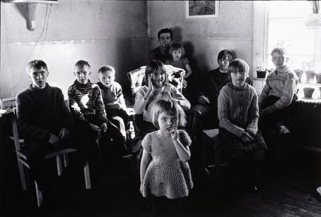 Mustavalkoinen kuva, jossa kymmenen henkilöä istuu tai seisoo huoneessa.