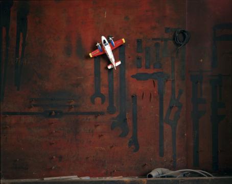 Lelulentokone punaisella ruosteisella alustalla, johon on maalattu mustalla eri työkalujen siluetteja.