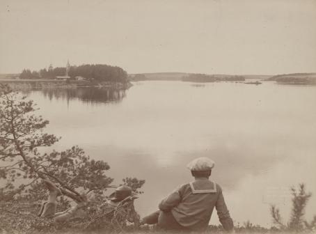 Mustavalkoisen kuvan etualalla on kaksi henkilöä katselemassa järvimaisemaa.