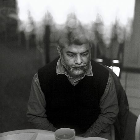 Mustavalkoisessa kuvassa mies istuu pöydän ääressä. Hänellä on parta, kauluspaita ja musta liivi. Pöydällä hänen edessään on kuppi.