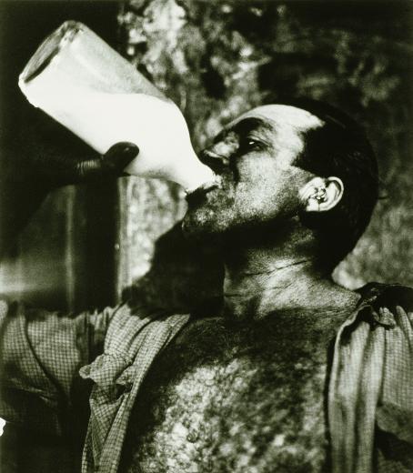Mustavalkoisessa kuvassa mies juo maitoa lasipullosta.