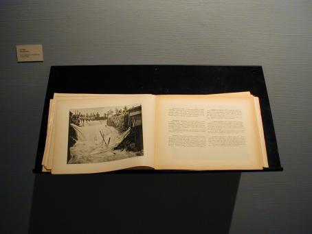 Näyttelyssä esillä oleva kirja, jossa näkyy Inhan valokuva koskesta sekä tekstiä, josta ei saa selvää.