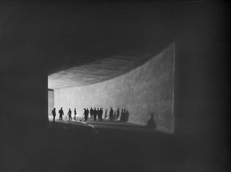 Mustavalkoisessa kuvassa henkilöitä käytävässä, joka on muuten tumma mutta jostain tulee valoa joka valaisee heidät.