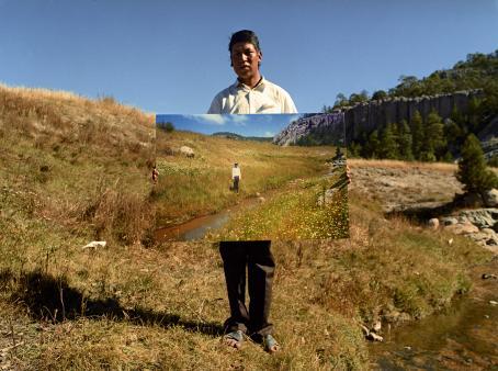 Henkilö seisoo pitäen valokuvaa, jossa on lähes samanlainen maisema kuin missä hän seisoo.