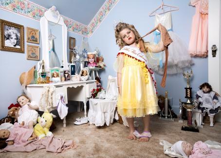 """Pieni tyttö keltaisessa mekossa seisoo huoneessa. Hänellä on meikkiä ja laitetut hiukset, ja päässä tiara. Hänen olallaan on nauha, jossa lukee """"Little Miss Colorado"""". Hänen kaulan ympärillään on sukkahousut joita hän vetää kädellään. Huoneessa on kampauspöytä, mekkoja ja nukkeja."""