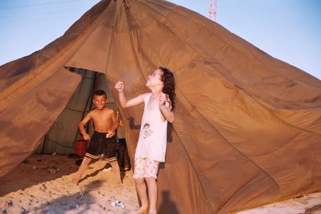 Teltan edustalla auringonpaisteessa kaksi lasta hymyilevät leveästi.