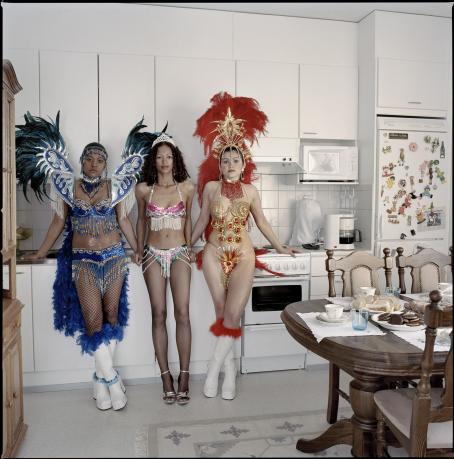 Kolme naista nojaa keittiön työtasoa vasten. Heillä on päällään samba-asut.