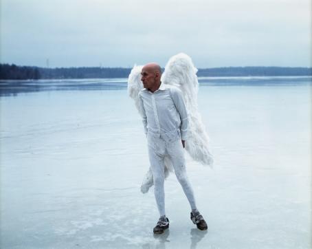 Vanha mies valkoisissa vaatteissa ja valkoiset enkelinsiivet selässään seisoo järven jäällä sinisävyisessä maisemassa.