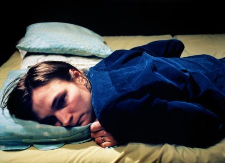 Henkilö sinisessä paidassa makaa mahallaan sängyllä. Hänen vieressään on tyhjä paikka.