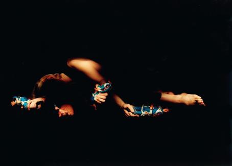 Muuten täysin musta, paitsi keskellä on osittain valaistu henkilö, joka pitää kädessään lelufiguuria. Figuuri näkyy kolmessa eri kohdassa.