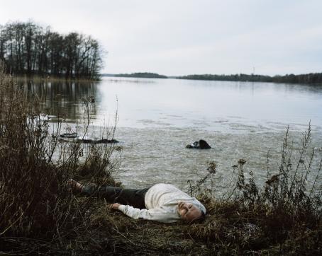 Henkilö makaa selällään järven rannalla rantakasvillisuuden keskellä.