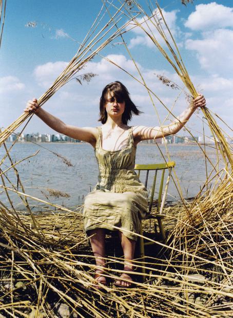 Nainen istuu tuolissa kaislikossa ja pitelee molemmissa käsissään kaislatuppoja. Hänen takanaan näkyy merenlahti sekä kaupunkia.