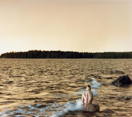 Aallokko, jonka taustalla näkyy metsää. Kivellä istuu alaston ihminen polvet koukussa, aalto lyö hänen jalkoihinsa.