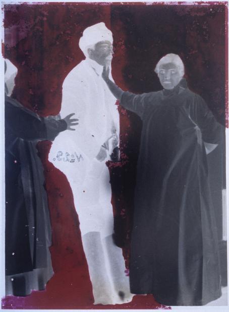 Negatiivikuva, jossa kaksi tummaa hahmoa ja yksi vaalea hahmo punaista taustaa vasten.