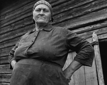 Mustavalkoinen kuva vanhasta naisesta. Hänen taustallaan näkyy hirsiseinää.