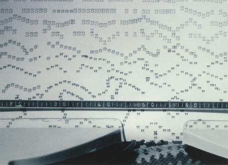 Kirjoituskoneessa oleva paperi, johon on kirjoitettu aaltoileviin jonoihin kirjaimia ja välimerkkejä.