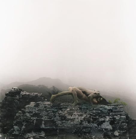 Kivimuurin päällä kaksi alastonta ihmistä intiimisti lähekkäin. Takana sumuista maisemaa ja vuoria.