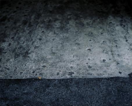 Yläreunassa vaaleamman harmaata kivipintaa, alareunassa kaistale tummemman harmaata kivipintaa.