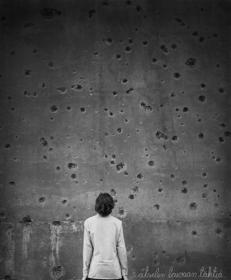 Mustavalkoisessa kuvassa henkilö seisoo katselemassa kiviseinää, jossa on erikokoisia kuoppia ja reikiä.