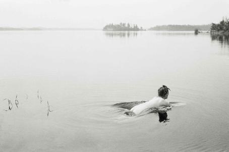 Mustavalkoinen järvimaisema, jossa alaston nainen on juuri kastautumassa veteen.