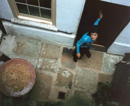 Ylhäältä päin otetussa kuvassa sinipaitainen nainen on oviaukossa ja pitää toisella kädellään ovea auki takanaan.