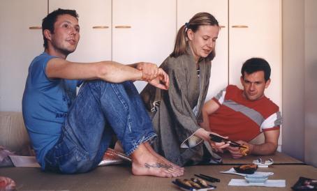 Kaksi miestä ja yksi nainen istuvat vierekkäin. Naisella on syömäpuikot ja hän on ottamassa ruokaa.