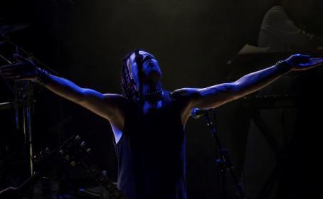 Henkilö seisoo mikrofonin takana kädet levitettyinä sivuille ja katsoo ylöspäin. Häneen kohdistuu sinistä valoa.