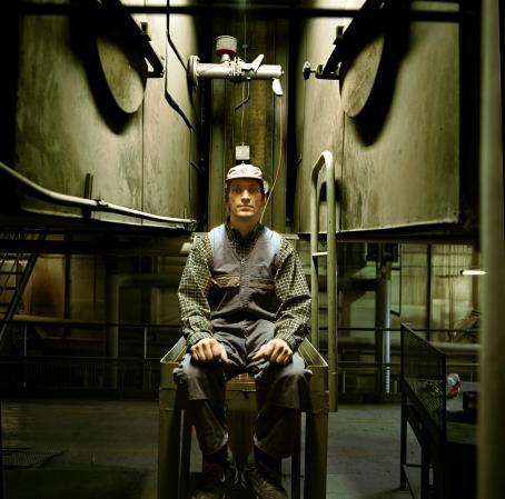 Mies istuu haalarit päällä tehdasmaisessa ympäristössä.