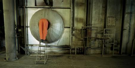 Näkymä tehtaasta. Vasemmassa reunassa oranssihaalarinen henkilö seisoo jakkaran päällä kurkistamassa putkeen, ja hänestä näkyvät vain jalat.