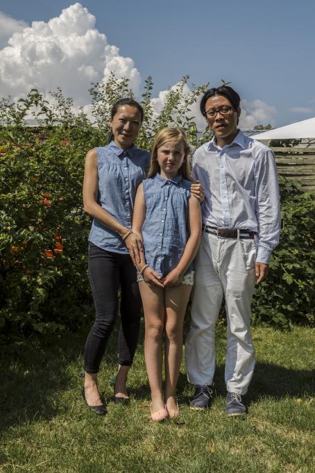 Nainen, mies ja lapsi seisovat nurmikolla vihreän pensaan edessä. Heillä kaikilla on sininen paita, naisella ja lapsella täysin samanlainen. Naisella on toinen käsi lapsen olkapäällä ja toinen lapsen käsivarrella.