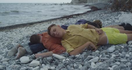 Rantakivikossa makaa kolme ihmistä päällekkäin. Alimmainen on mahallaan, toinen makaa mahallaan pää hänen jalkojensa päällä, ja kolmas makaa selällään toisen selän päällä.