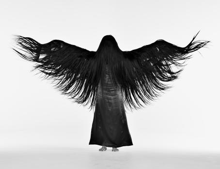 Mustavalkoisessa kuvassa seisova henkilö on levittänyt kätensä niin, että hapsuinen kangas on levinnyt ja näyttää kuin hänellä olisi siivet.