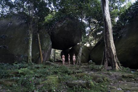 Metsässä seisoo vierekkäin kolme alastonta naista. Yksi on selin, yksi sivuttain ja yksi kasvot kameraan päin. Maassa kasvaa erilaisia kasveja, pari puuta ja naisten takana on iso kivi, joka on muiden isojen kivien päällä niin, että sen alta pääsee kulkemaan.