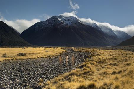 Soratiellä seisoo vierekkäin kolme alastonta naista. Yksi on selin, yksi sivuttain ja yksi kasvot kameraan päin Heidän takanaan näkyy korkeita vuoria, ja ympärillä heinikkoa.