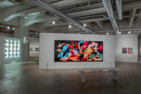 Näyttelyssä esillä oleva iso teos, jossa mustalla pohjalla on erivärisiä, erikokoisia osittain läpinäkyviä muotoja, jotka osin menevät toistensa päälle.