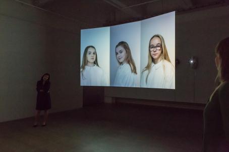 Näyttelytilassa oleva teos jossa on vierekkäin kolme muotokuvaa, joissa olevilla nuorilla on valkoiset albat päällään.