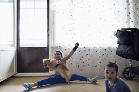 Veljekset Fernando ja Leonardo Stoica leikkivät koiransa kanssa kotonaan Vantaan Myyrmäessä kesäkuussa 2015. Kuva: Heidi Piiroinen.