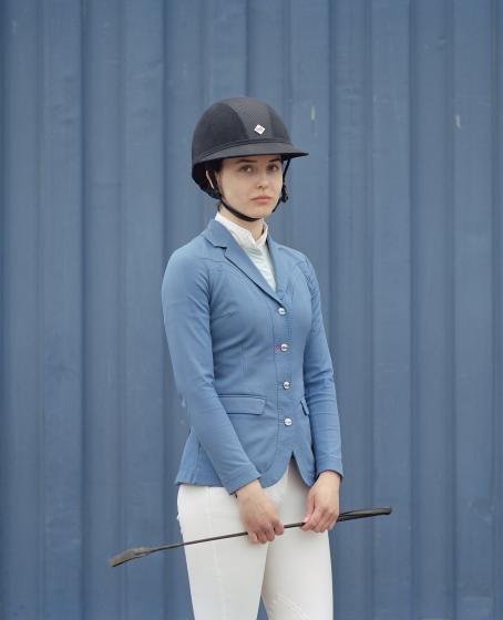 Nuori nainen sinisessä takissa ja valkoisissa housuissa seisoo sinisen lautaseinän edessä. Hänellä on päässään kypärä ja käsissään raippa.