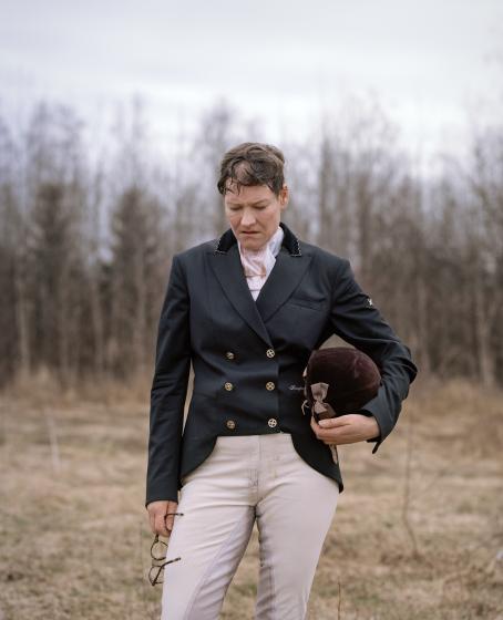 Nainen ratsastusvaatteissa seisoo pitäen toisessa kädessä kypärää ja toisessa silmälaseja. Hän katsoo maahan ja suupielet ovat kääntyneet alaspäin. Taustalla on ruskeanharmaa maisema.