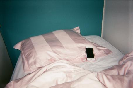Petaamaton sänky, jossa on vaaleanpunaiset petivaatteet. Tyynyllä on puhelin. Sänky on nurkassa, ja toinen seinä on turkoosi ja toinen valkoinen.