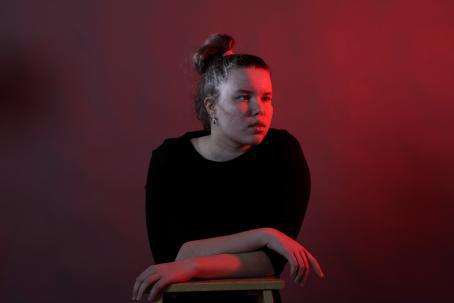 Muotokuva nuoresta naisesta, joka nojaa käsillään tuoliin tai pieneen pöytään. Oikealta tulee punaista valoa.