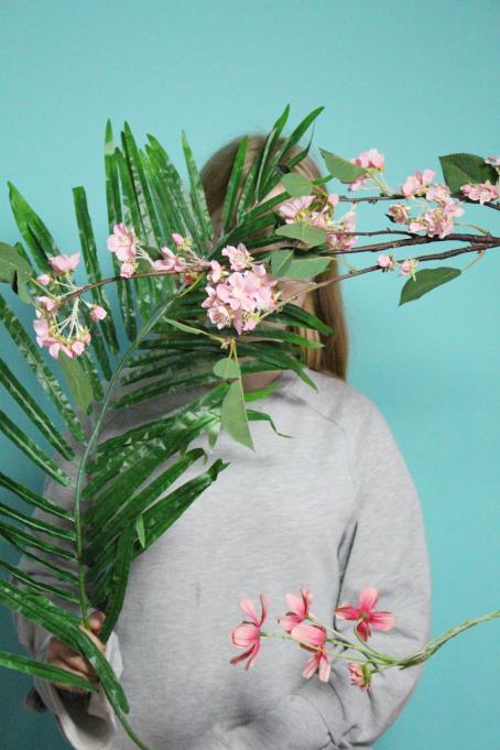 Harmaapaitainen henkilö pitää kädessään vihreitä oksia, joissa on vaaleanpunaisia kukkia. Oksat peittävät hänen kasvonsa. Tausta on vaaleansininen.
