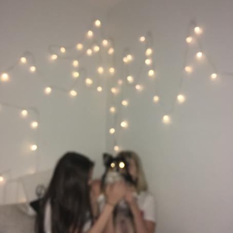 Epäterävässä kuvassa kaksi nuorta istuvat sängyllä, toinen heistä pitää koiraa sylissä. Koiran silmät näkyvät valopisteinä. Valkoisella seinällä roikkuu valosarja.